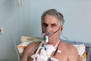 Patient in hospital with oxygen mask wearing BeHear ACCESS hearing headset